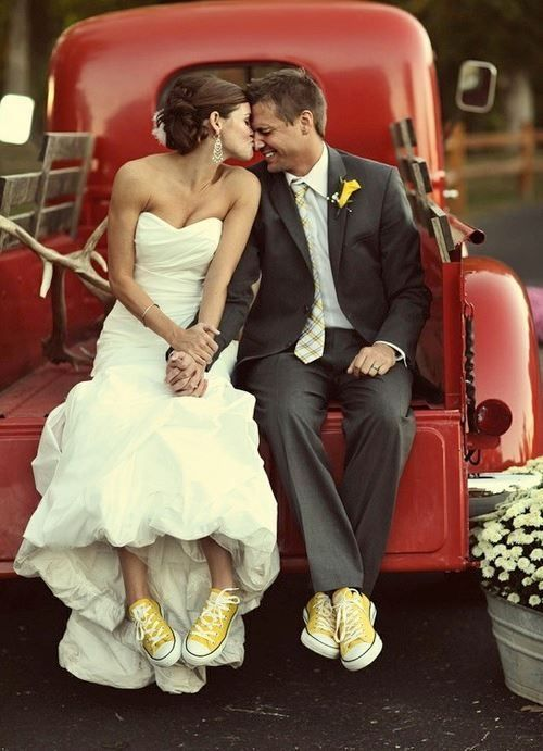 Bride and Groom kissing on back of red car with matching yellow Converses