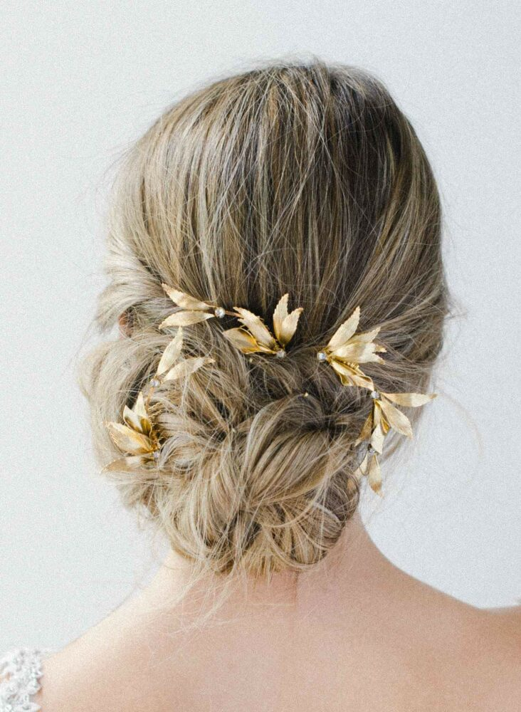 Bride wearing gilded floral branch pin accessory