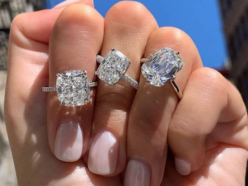 A hand displaying 3 engagement rings