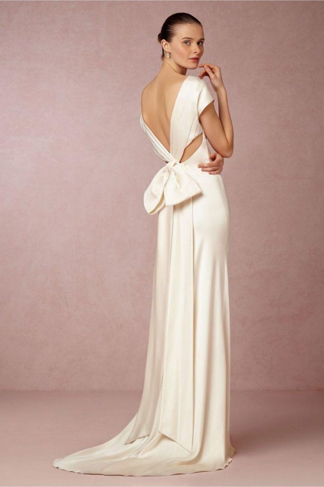 Bride wearing slip wedding dress with oversized bow on back