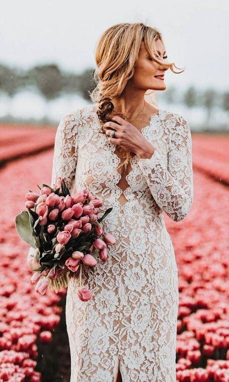 Boho bride wearing long sleeve lace sheath wedding dress