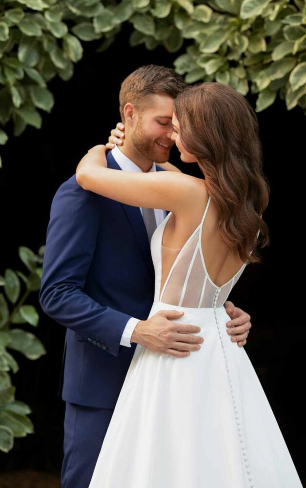 groom hugging bride wearing A-line wedding dress with sheer back