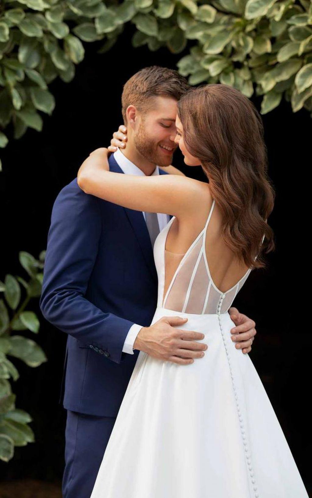 groom hugging bride wearing A-line wedding dress with sheer back