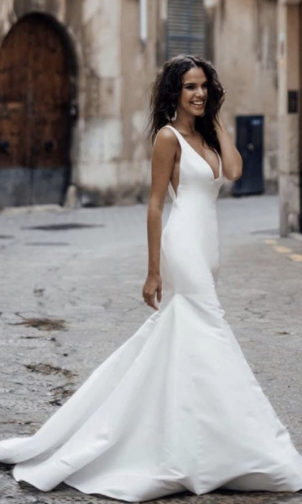bride walking in elegant simple trumpet bridal gown with v neckline