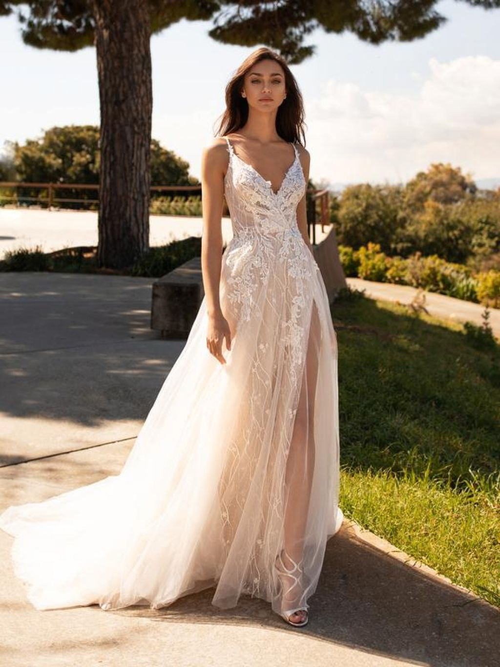 Bride in a-line wedding dress with high slit decorative lace by Pronovias