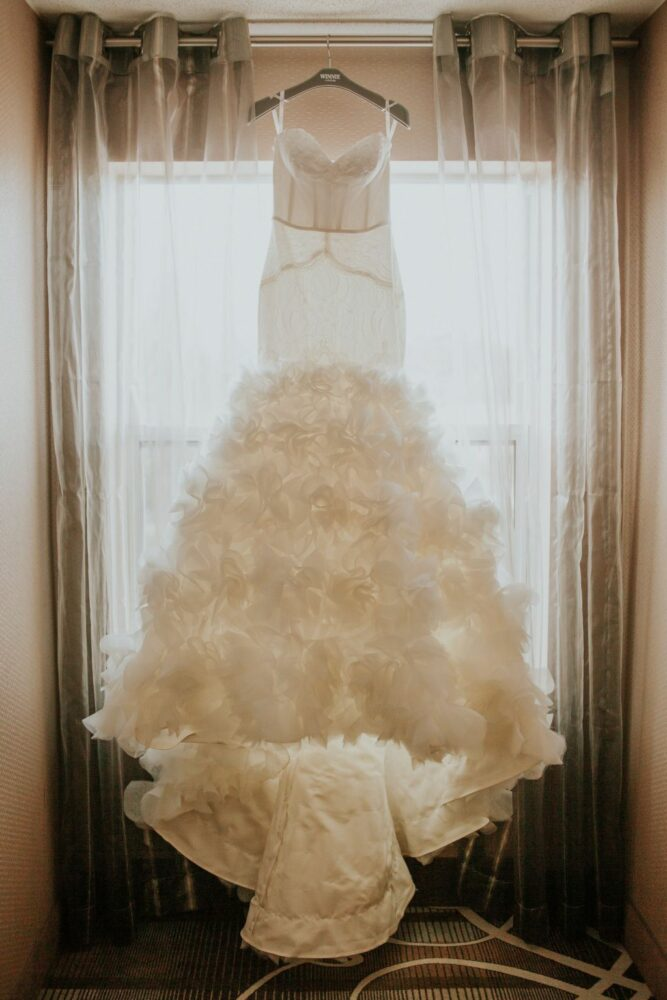custom made Winnie Couture trumpet bridal gown hanging on display in window