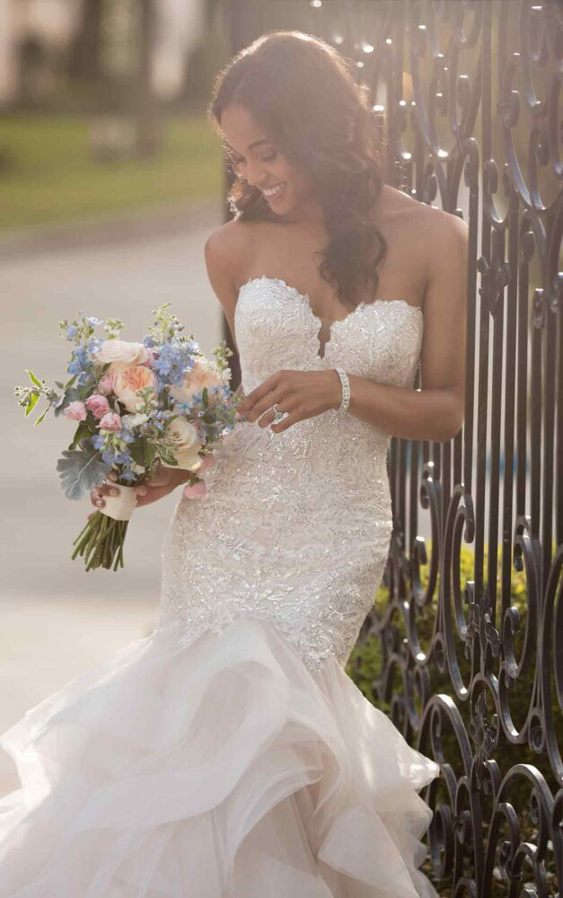 Bride looking at her bouquet while wearing Stella York 6750